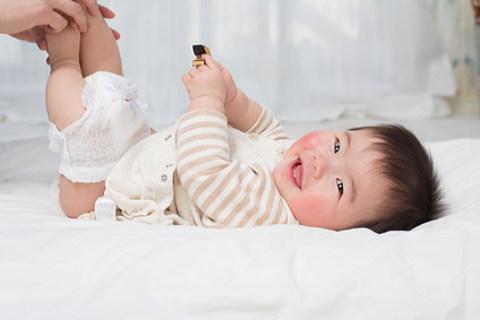 オムツを替てえ貰って笑顔の赤ちゃん