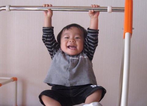 ぶら下がり健康器にチャレンジする赤ちゃん