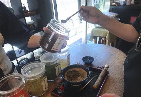 瓶に入った七味の材料をスプーンですくって鉢に移してるところ
