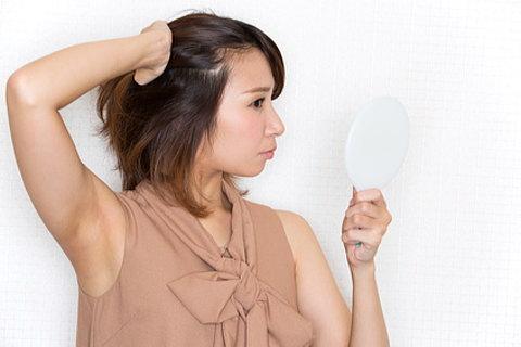 手鏡で白髪チェックする女性