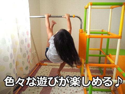 室内ジャングルジムに付いてる鉄棒で遊ぶ女の子