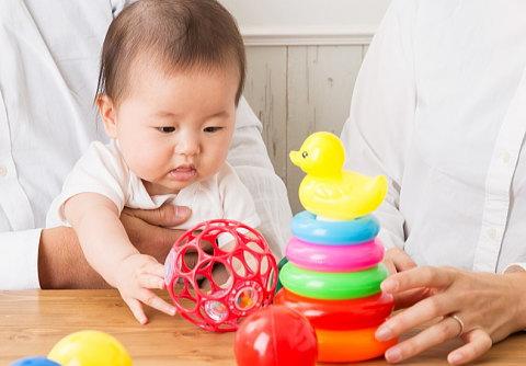 ママとパパと一緒にオーボールで遊ぶ赤ちゃん
