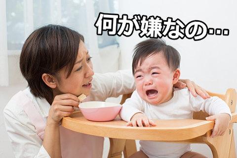 離乳食タイムにぐずってベビーチェアから抜け出そうとする赤ちゃん